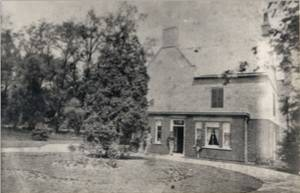 South side of The Grange with the owner Mr. J.G.Branstone standing in the doorway. The main drive is behind the trees to the left. - 1866.